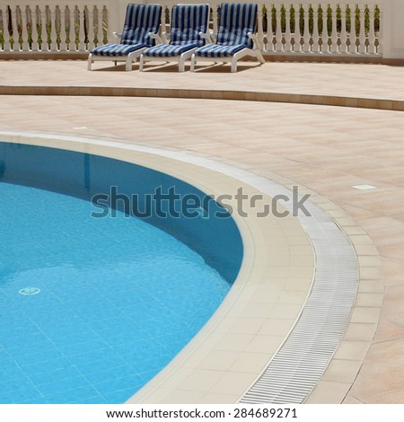 Detail from open air swimming pool with clean blue water and pool chairs