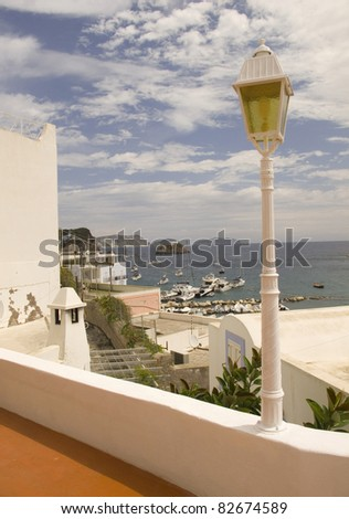 Detail from Ponza, Italy - Whitewashed lamppost in the foreground with sea in the background