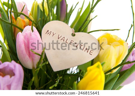 Detail from tulips in pink vase with Valentines heart - stock photo