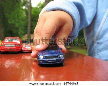 Detail hand with toy-car. Little baby play outdoor with toy - stock photo