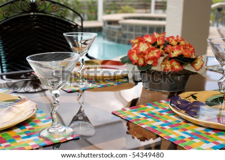 detail image of a table set for dinner on an outside patio or lanai with swimming pool in background, the patio is screened in. - stock photo