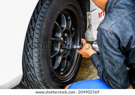 Detail image of mechanic hands with tool, changing tyre of car, with