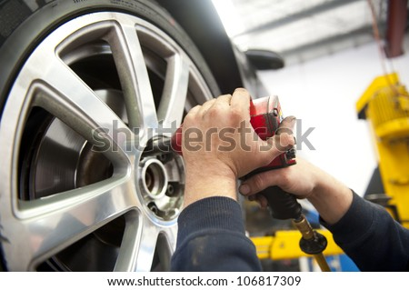 Detail image of mechanic hands with tool, changing tyre of car, with blurred background of garage. - stock photo