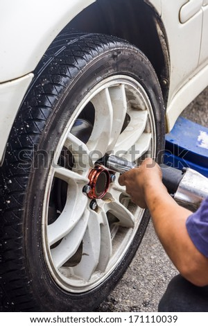 Detail image of mechanic hands with tool, changing tyre of car, with blurred background of garage. Soft focus with motion on hand. - stock photo