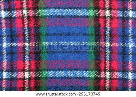 Detail od blue-red-white-green checkered tartan wool blanket with fringe.
