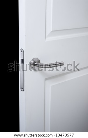 detail of a an open door whit lock handle, and black background - stock photo