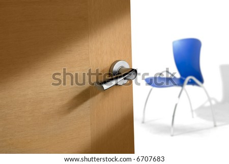 detail of a an open door with a luxury lock handle, and blurry blue chair on background - stock photo