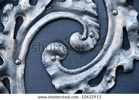 Detail of a ancient metal door with spiral silver decoration - stock photo