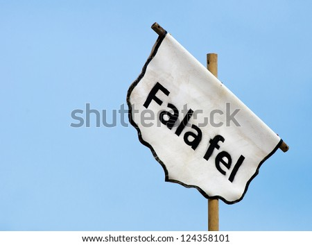 Detail of a banner locating a falafel market stand.
