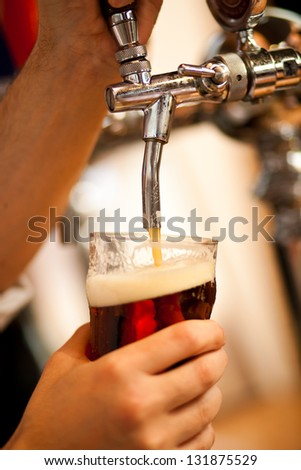 Detail of a bartender drawing a beer - stock photo