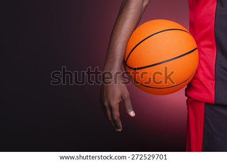 Detail of a basketball player holding a ball against dark background - stock photo