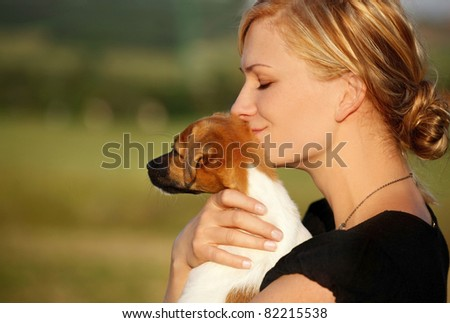 Detail of a beautiful blond woman smiling with eyes closed holding a puppy in her arms - stock photo