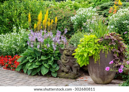 Detail of a beautiful summer garden with an interlocking stone walkway. - stock photo