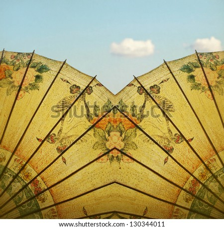 Detail of a beautiful vintage decorative rice paper chinese umbrella on blue light sky with cloud in the background - stock photo