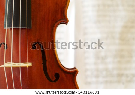 Detail of a beautiful violin with a blurred musical score in the background. - stock photo