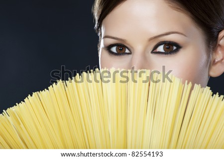 Detail of a beautiful woman's face half covered with spaghetti over black background - stock photo