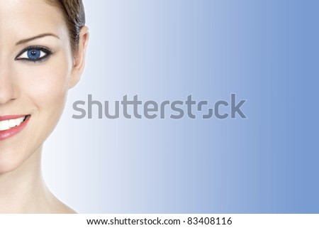 Detail of a beautiful woman's half face over light blue background