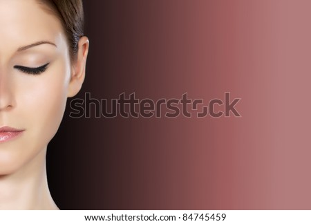 Detail of a beautiful woman's half face with eye closed over dark background - stock photo