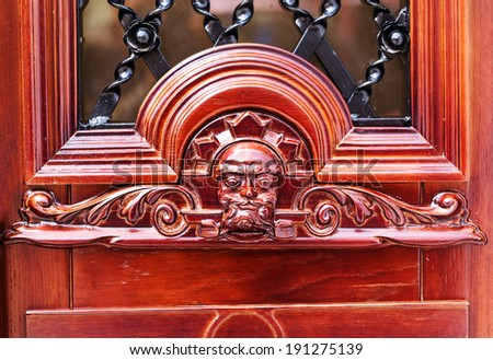 Detail of a beautiful wooden door with exquisite stylized carvings in the ancient traditional technique - stock photo