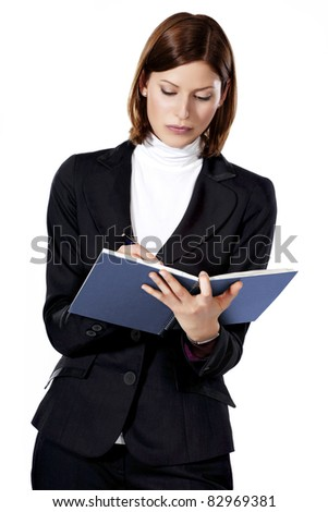 Detail of a beautiful young businesswoman writing and looking in a notebook
