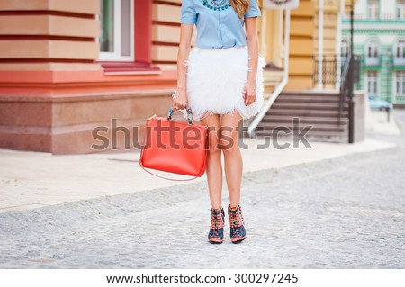 Detail of a beautiful young fashion woman with handbag and skirt in feathers posing in the city streets - stock photo