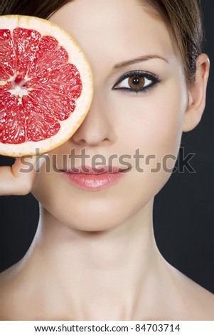 Detail of a beautiful young woman's face partly covered by grapefruit - stock photo