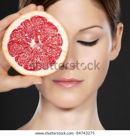 Detail of a beautiful young woman's face with eye closed, partly covered by grapefruit
