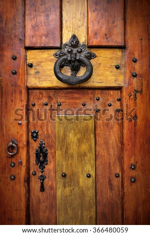 Detail of a brass door knocker on a wooden door decorated with rivets - stock photo