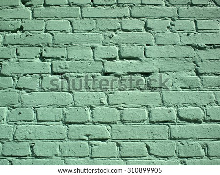 Detail of a brick wall the whole surface is painted with green paint. For use as background or wallpaper - stock photo