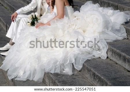 detail of a bride's dress seated on the ground with her groom - stock photo