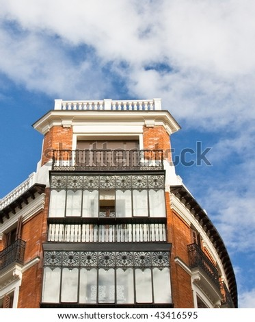 Detail of a building with terrace and blue sky with clouds - stock photo