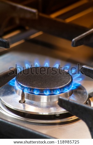 Detail of a burning gas stove with blue flames - stock photo