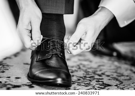 Detail of a business man lacing his shoes - stock photo