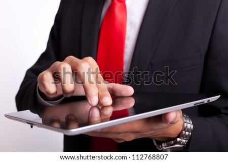 detail of a business man tapping and browsing on its new touch screen pad