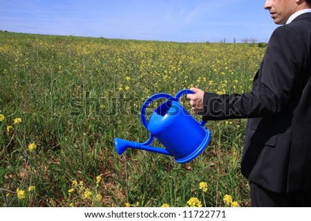 Detail of a business man with a blue watering can in a field