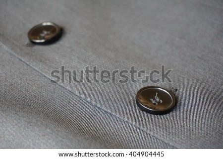 Detail of a button stitched to the fine gray suit (jacket)  - stock photo