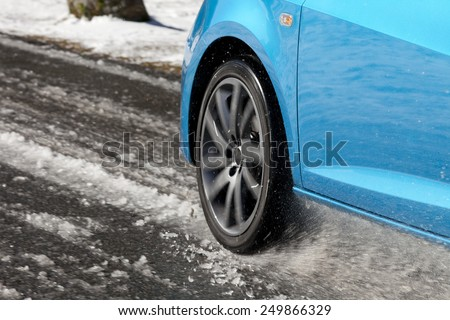 Detail of a car tire driving and splashing on the snow.  Driving on a snowy road