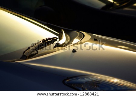 Detail of a car windshield wipers lit by low sunlight - stock photo