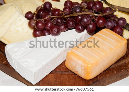 Detail of a cheese platter with grapes - stock photo