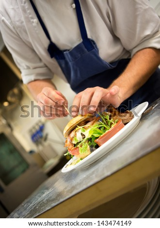 Detail of a chef preparing a gourmet burger - stock photo
