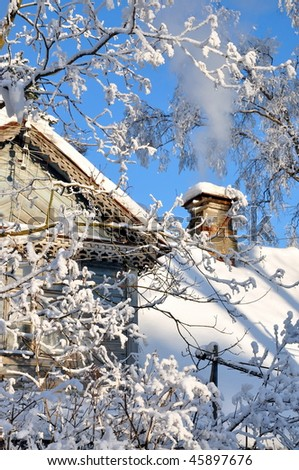 Detail of a chimney with smoke on a wooden roof in winter, blues sky - stock photo