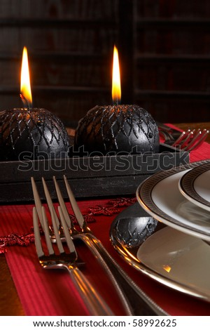 Detail of a christmas dinner table with red napkins and black candles - stock photo