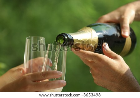 Detail of a couple preparing to celebrate with champagne - focus on bottle tip