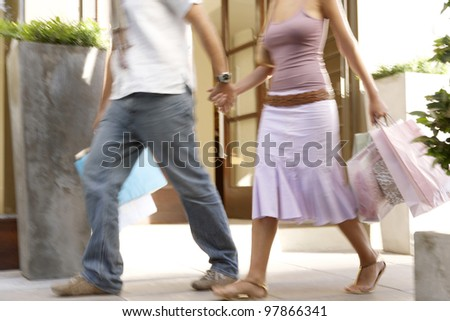 Detail of a couple walking down a shopping street with shopping bags, holding hands with motion blur - stock photo