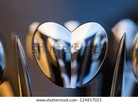 Detail of a cut glass champagne goblet with a heart on the side and reflecting lights from background - stock photo