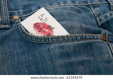 detail of a denim pocket holding a call me note - stock photo