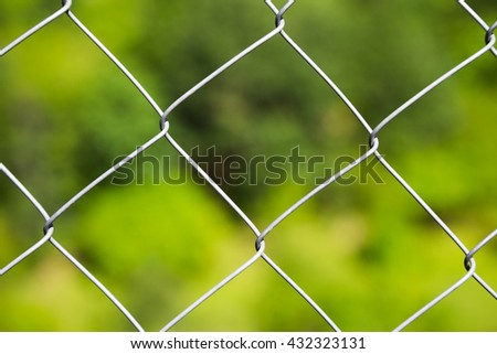 Detail of a diamond mesh wire fence with selective focus to the steel wire over a blurred green background - stock photo