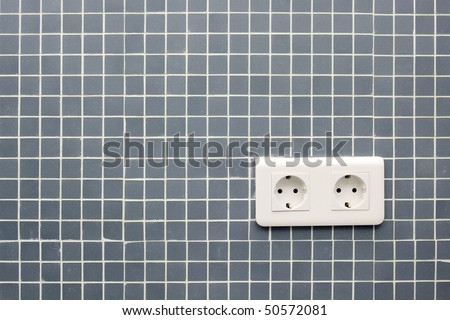 Detail of a double power European electric plug on tiled wall - stock photo