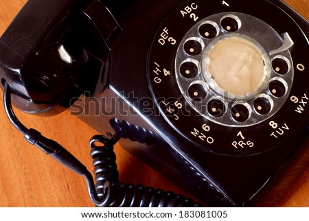 Detail of a dusty old black telephone. Closely cropped as viewed from above, the plastic telephone has a rotary dial with alpha numeric. The handset is on the cradle. The phone is on a wooden table.  - stock photo