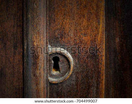 Detail of a dusty old keyhole in the door of a antique cabinet. The wood - Detail Dusty Old Keyhole Door Antique Stock Photo 704499007